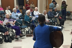 Life Enrichment Director Emily Sanderson leads the students in a song written by a resident of Mercy Retirement and Care Center.